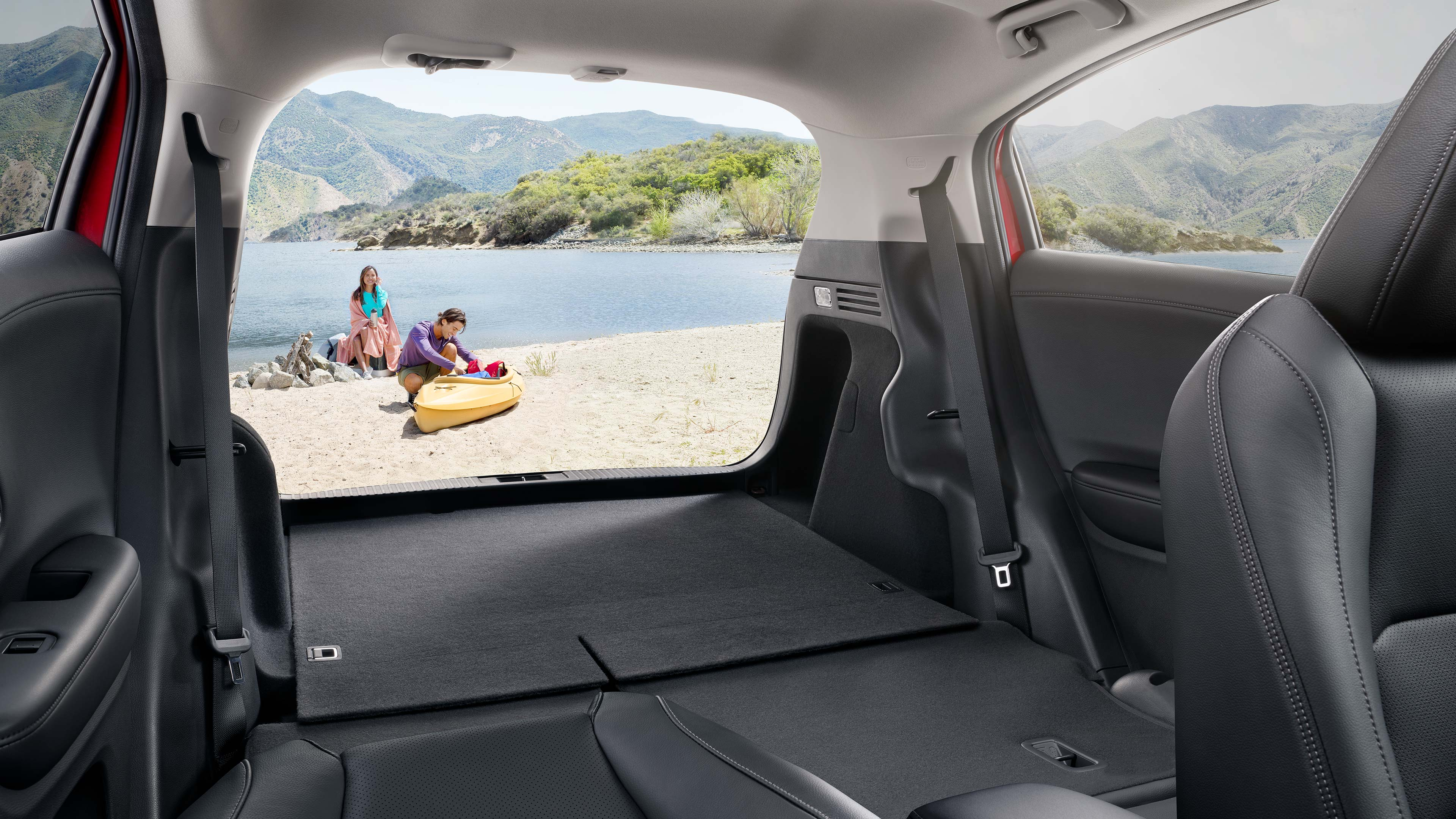 View through the back of the 2020 Honda HR-V with the seats down and people with a kayak on a beach behind it