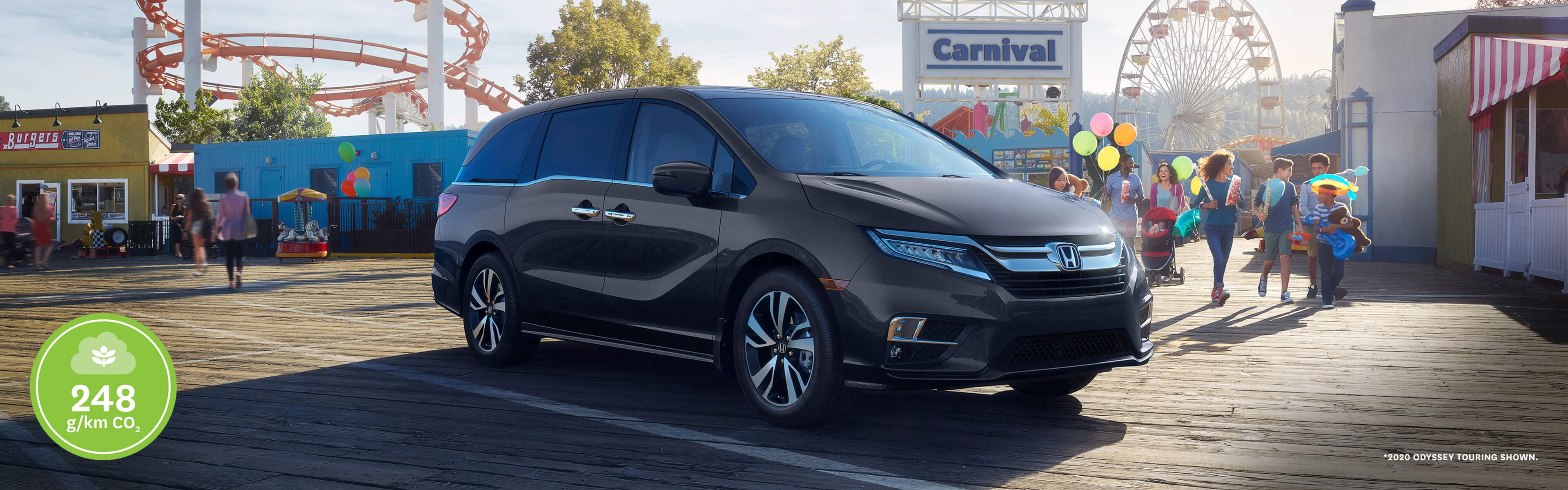2020 Honda Odyssey parked on a boardwalk in front of a carnival