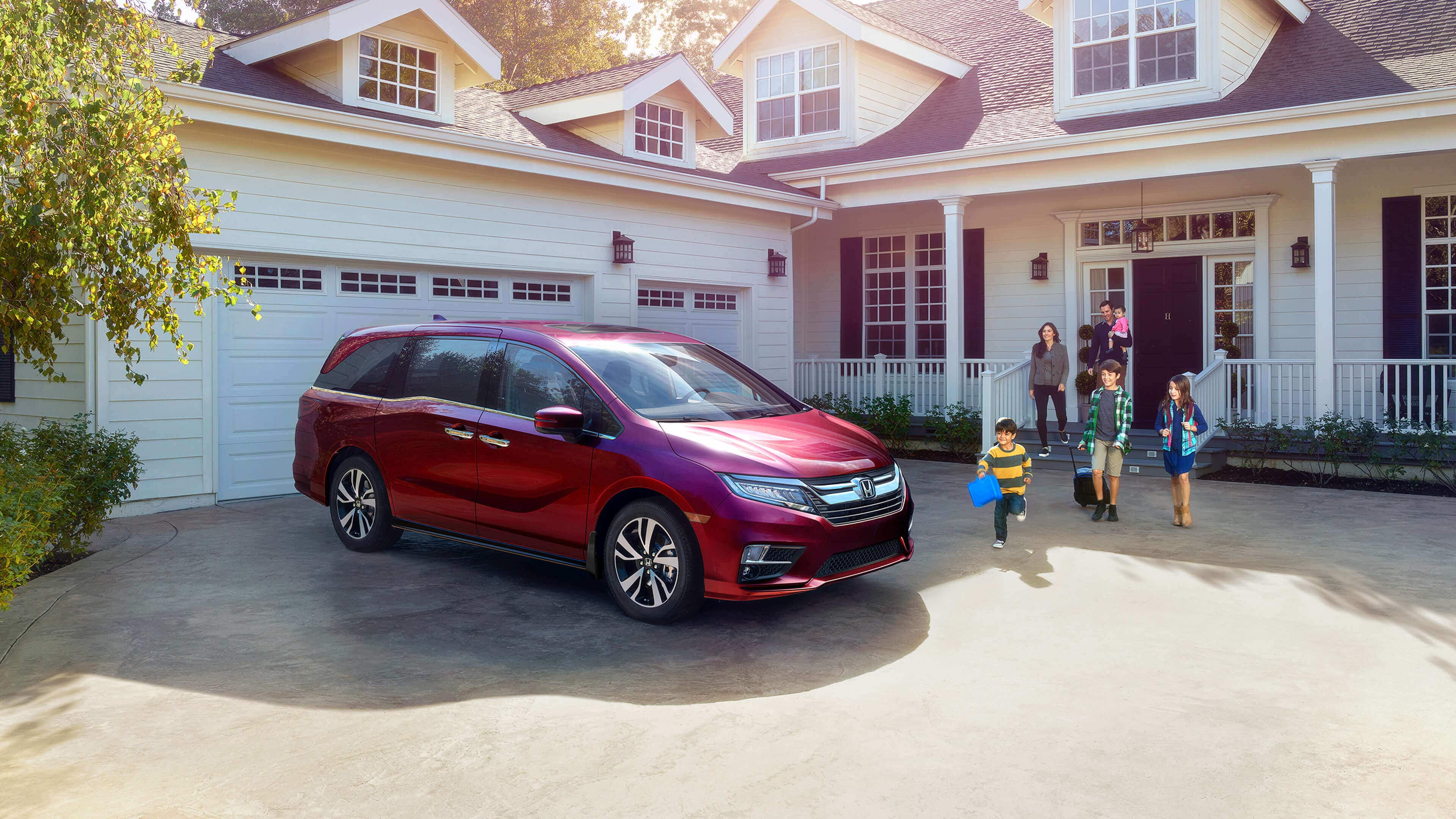 2020 Honda Odyssey parked in front of a garage with a family coming out to it from their house