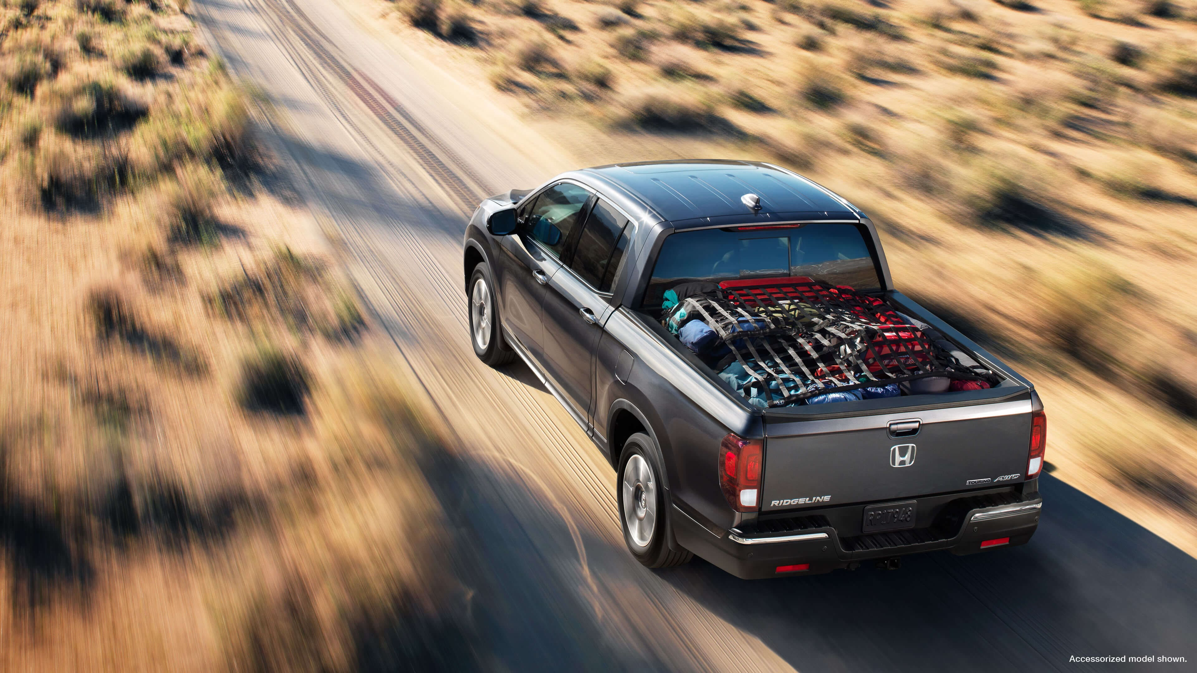 Overhead view of 2020 Honda Ridgeline driving on a country road with a full cargo bed