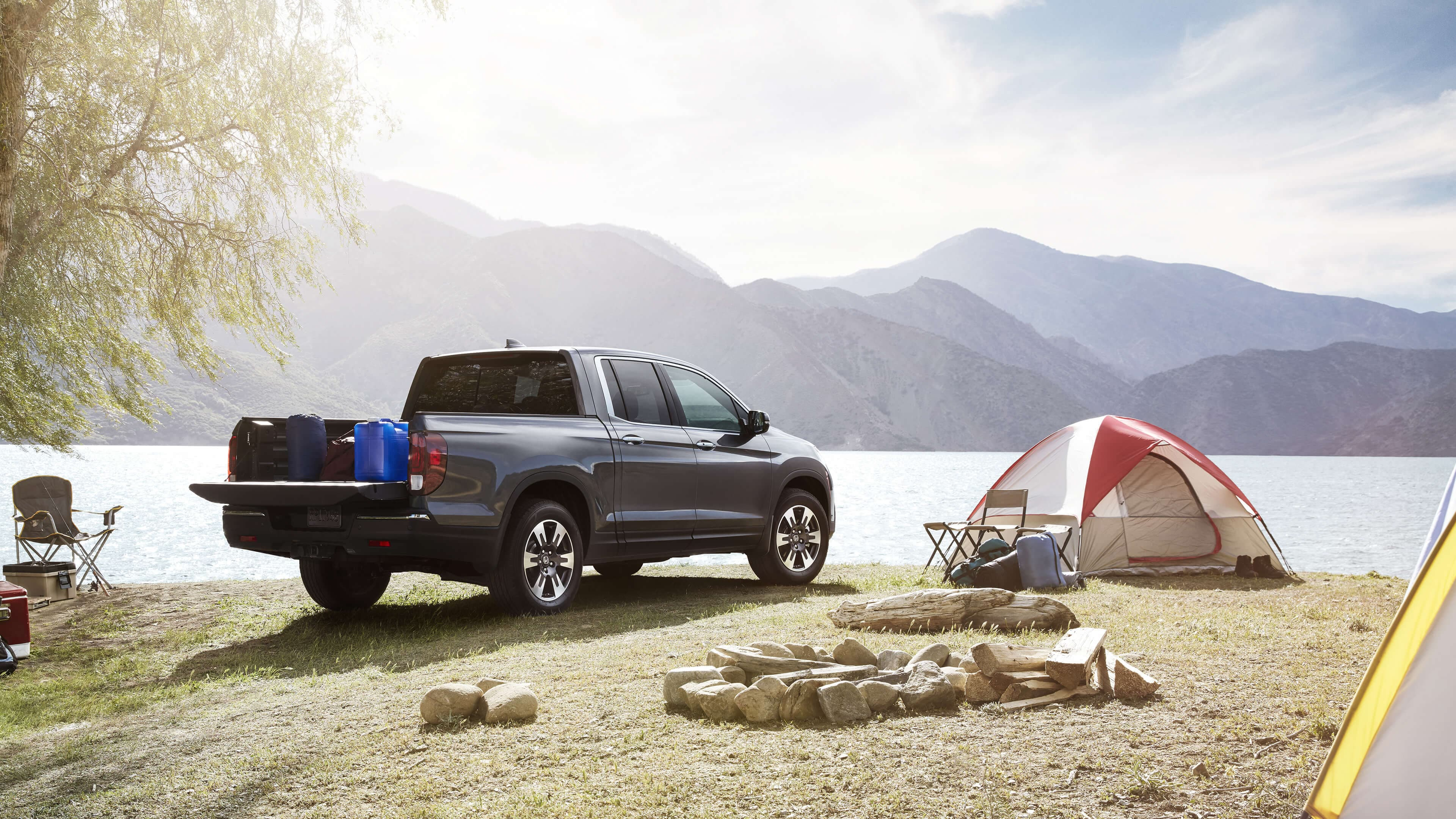 2020 Honda Ridgeline parked next to a tent and lake
