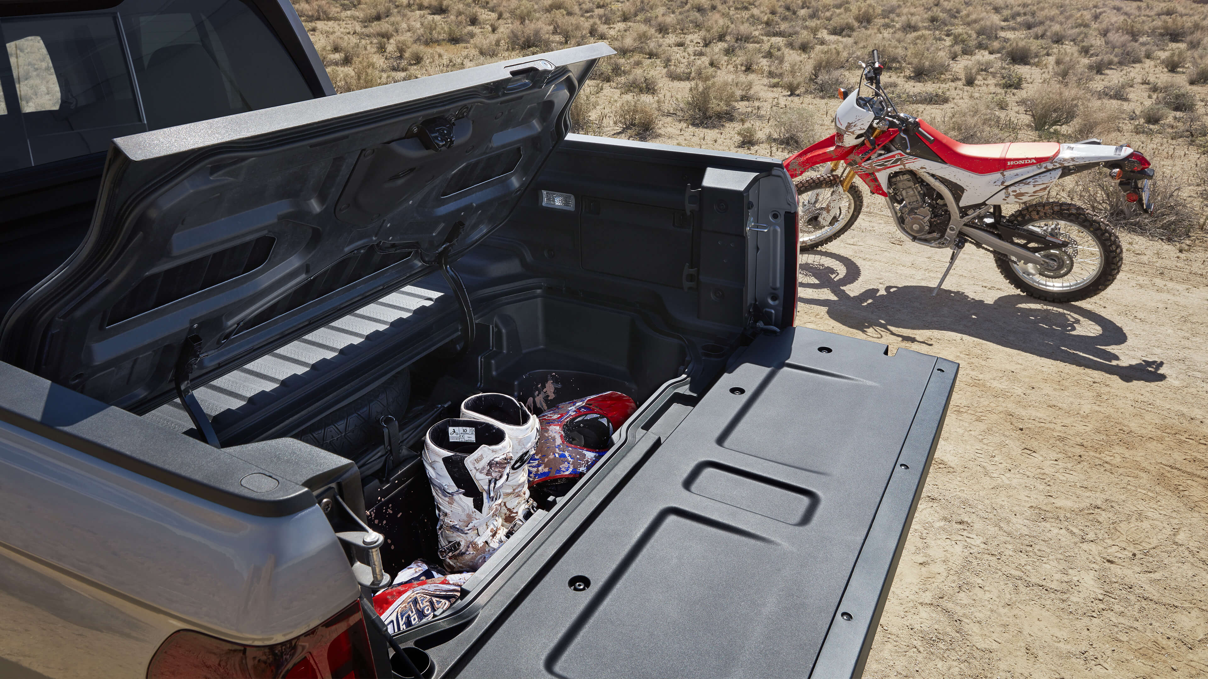 2020 Honda Ridgeline in-bed trunk open with dirtbike next to truck