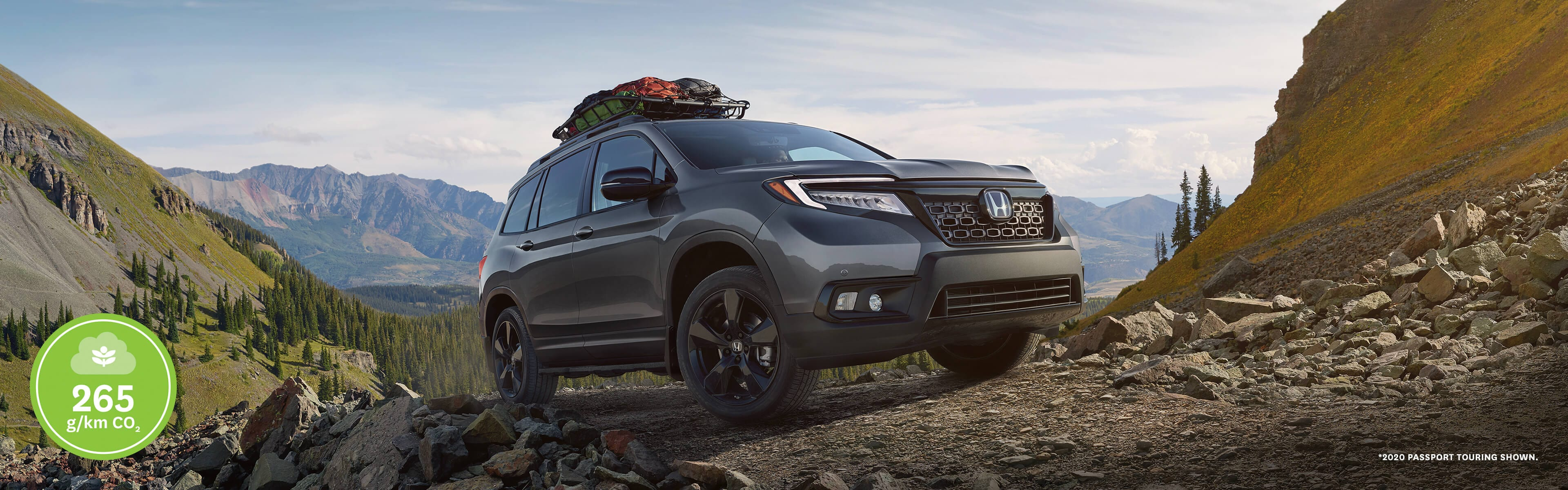2020 Honda Passport parked on rocks in a forest mountain area