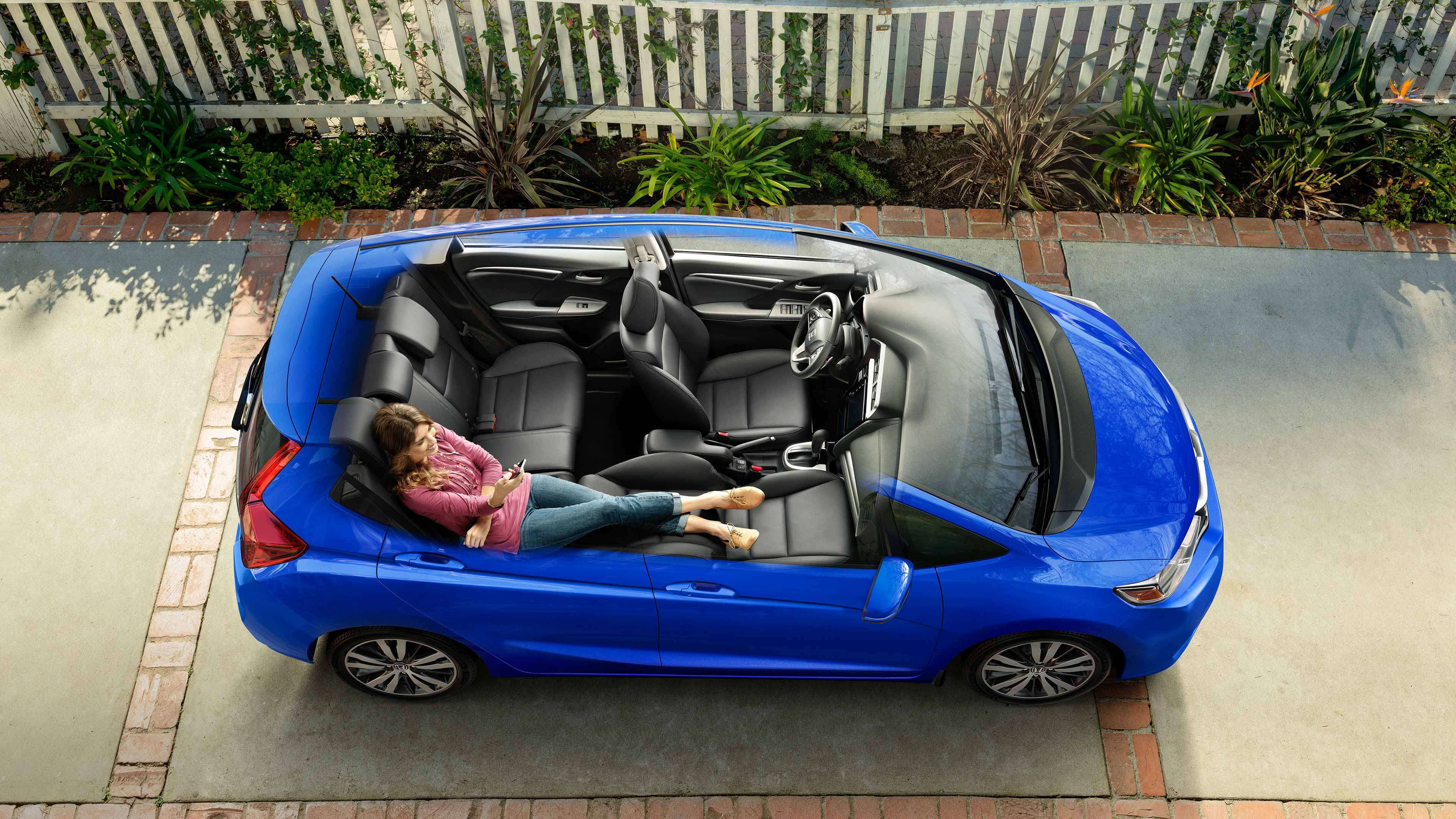 Overhead view of the Fit with an open view to see the interior with a woman sitting in the back with her feet on the front passenger seat and on her phone