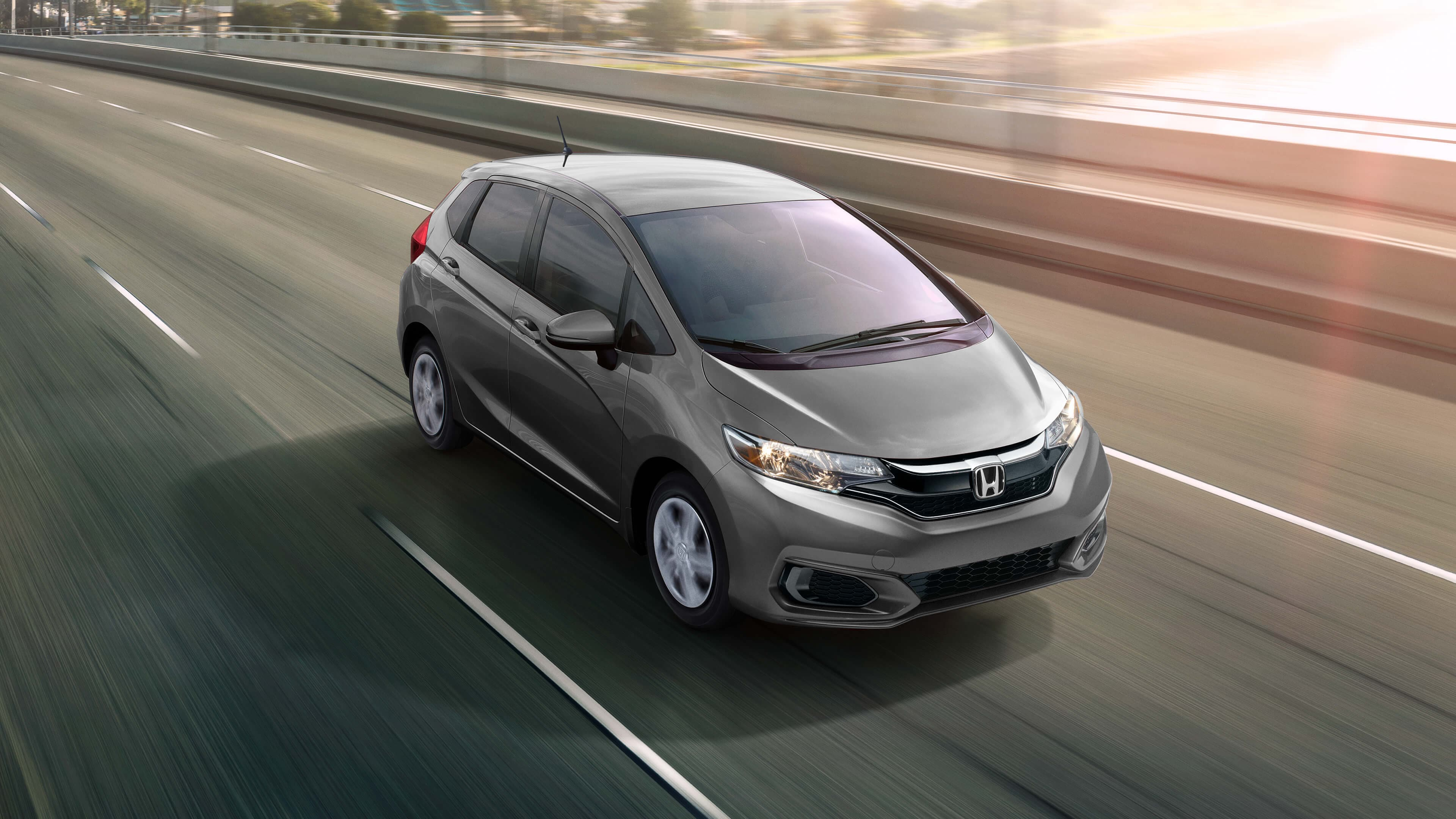 Honda Fit driving fast over a bridge
