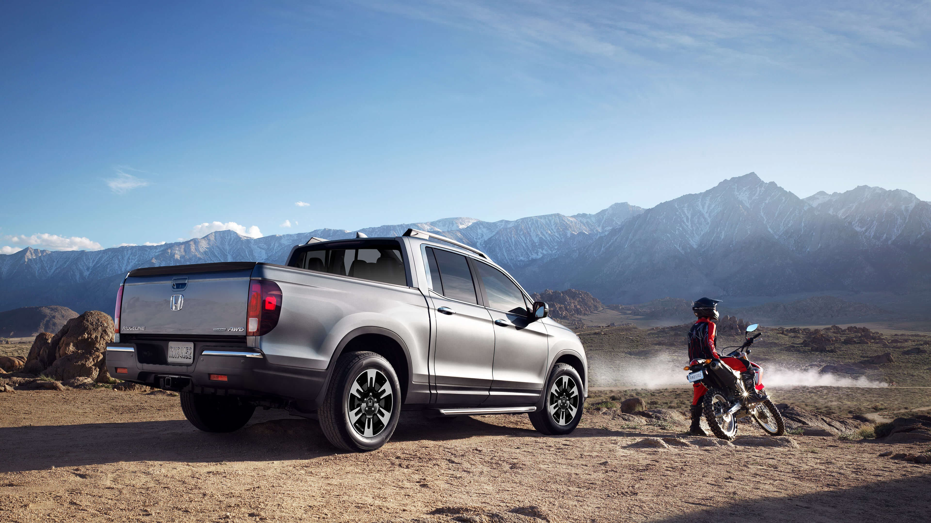 2020 Honda Ridgeline parked in front of the mountains with a dirtbiker right beside it